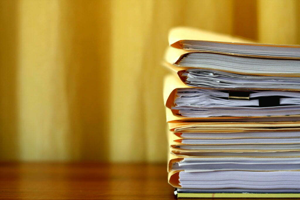A stack of paperwork, organized into manila folders, stacked on a desk.
