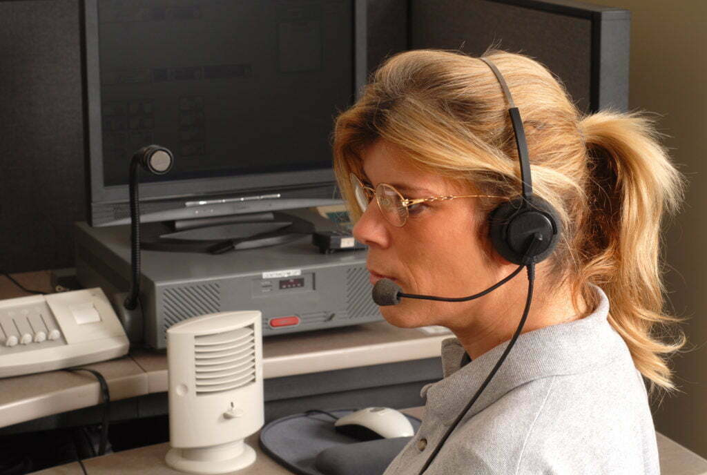 A police dispatcher sitting at a dispatch console wearing a microphone headset.