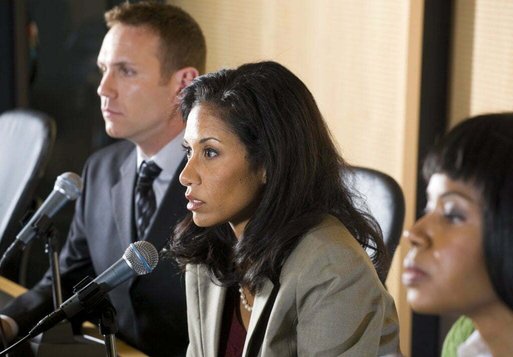 A female, African-American public information officer sits at a panel, speaking into a microphone during a press conference.