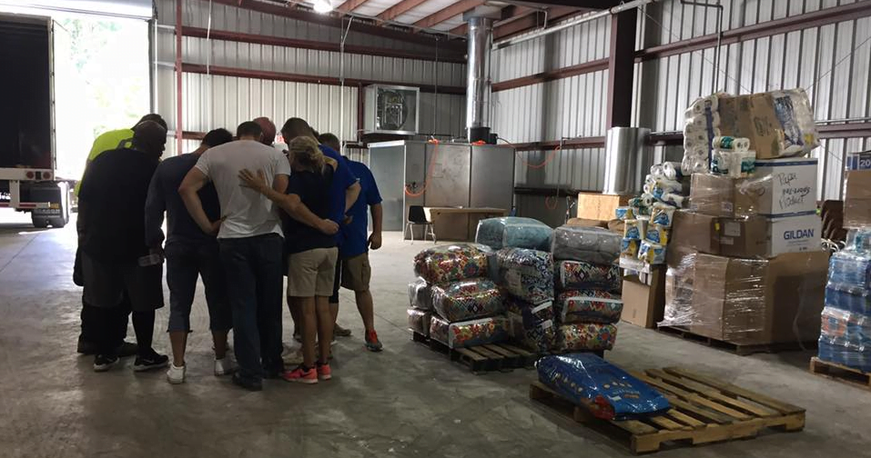 A group of volunteers meets in a circle in a disaster distribution site.
