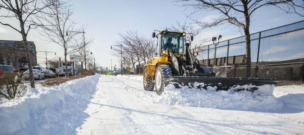 Big tractor with shovel remove thes snow from a sidewalk.