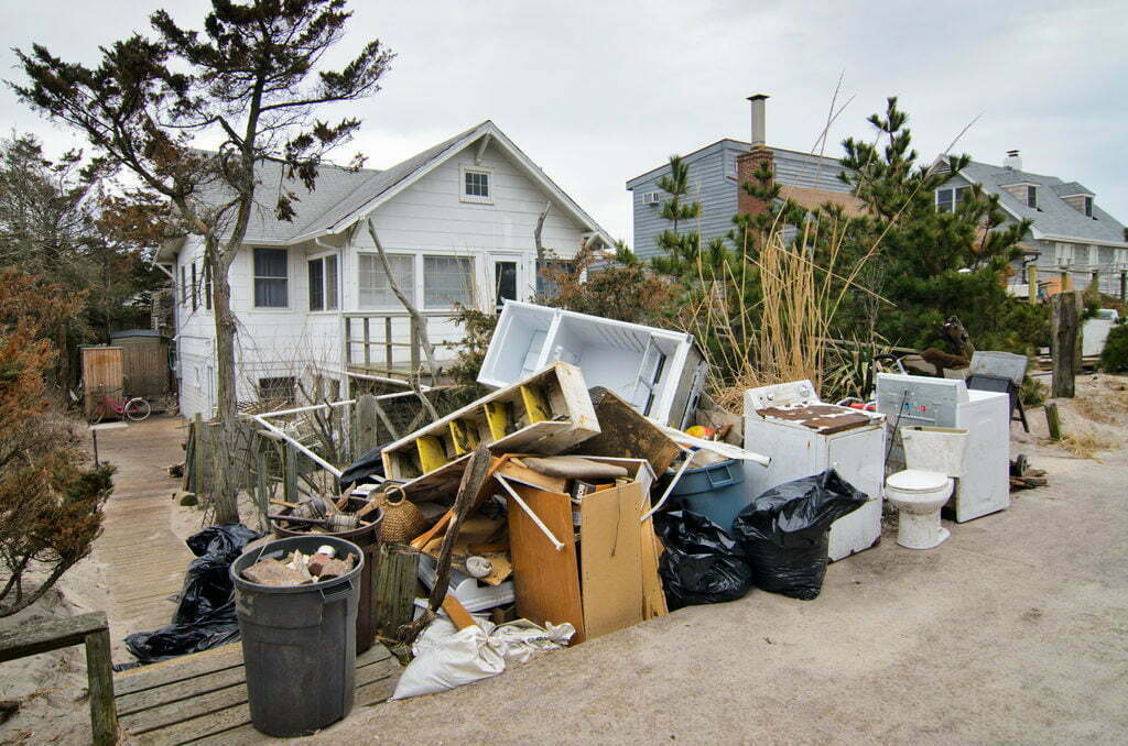 Large debris and white goods on the curb outside a home damaged in Hurricane Sandy.