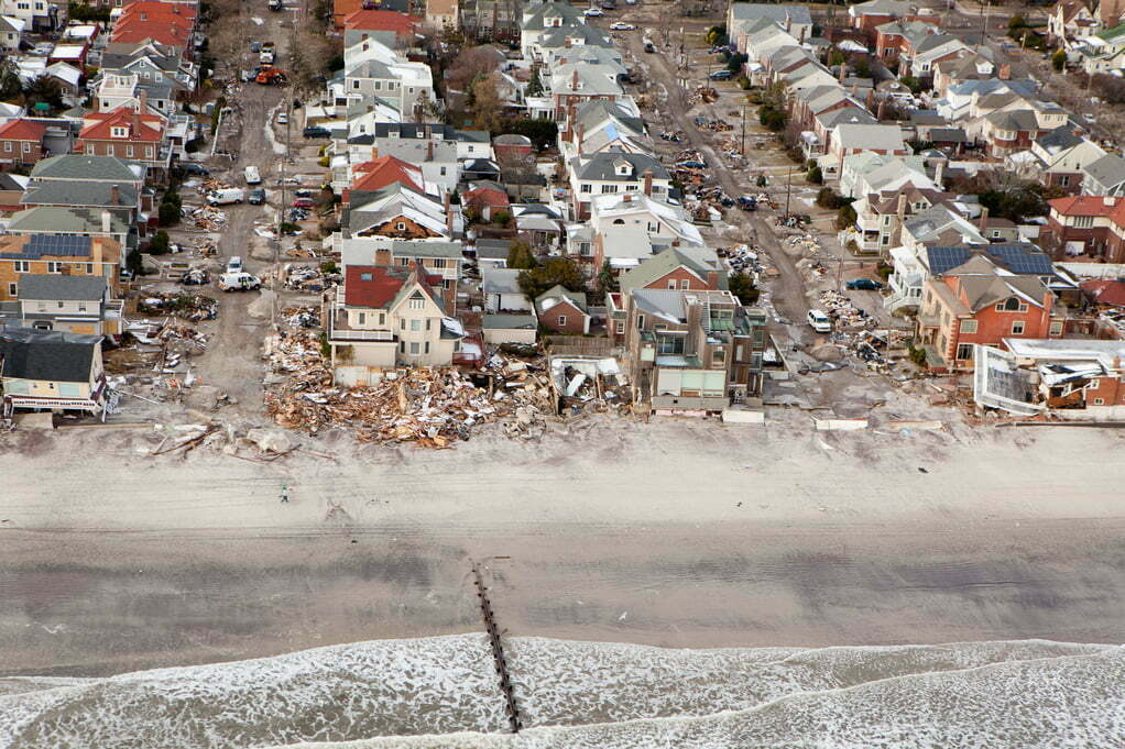 Aerial view of damaged homes and debris lined streets in a neighborhood hit by Hurricane Sandy.