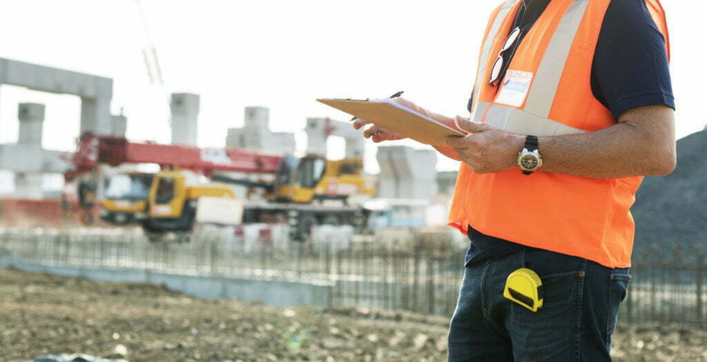 Torso of an orange-vested construction inspector on-site, holding a clipboard
