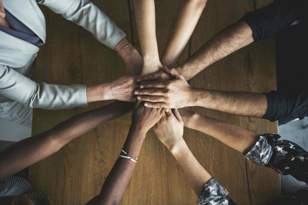 Shot from above, a diverse set of hands stacked in the center of a circle.