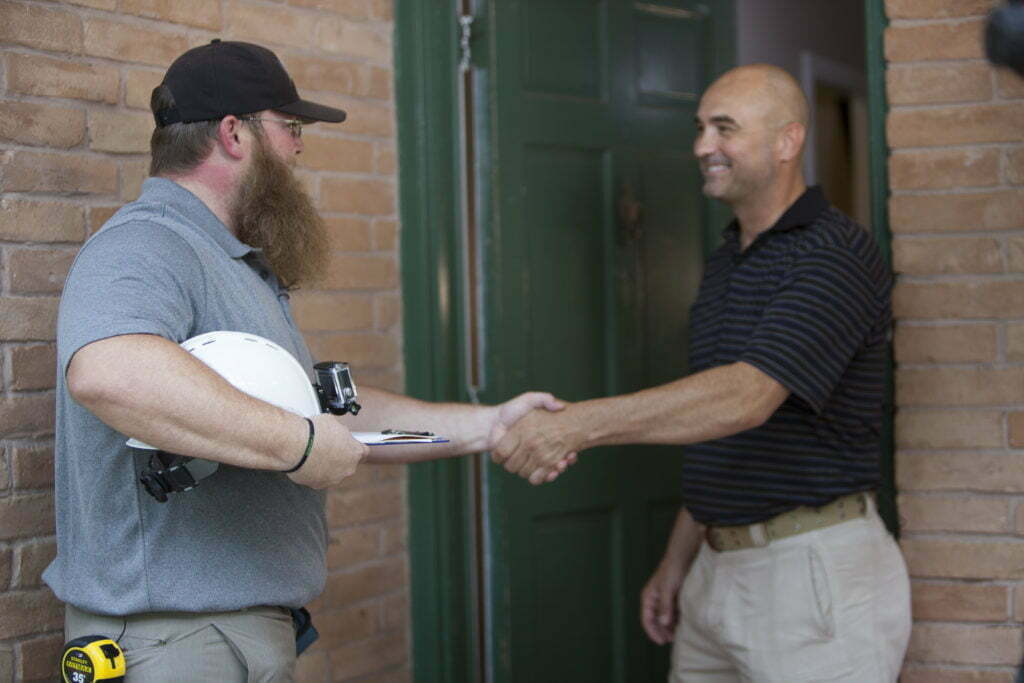An IBTS inspector shakes hands with a homeowner in front of the front door.