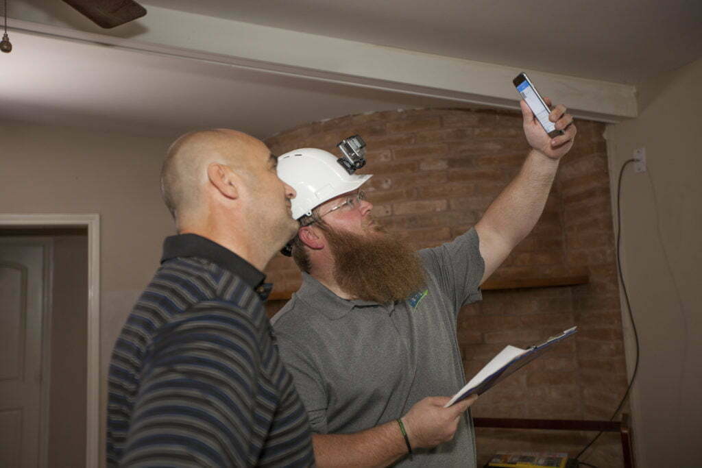 An inspector holds up his cell phone to photograph damage to the ceiling of a home, while the homeowner looks on.