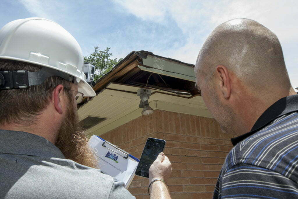 From behind, a damage inspector holding a cell phone and a homeowner examine damage to the exterior roof of home.