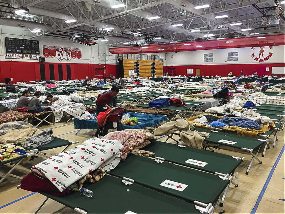 A high school gym setup as a disaster shelter with rows Red Cross cots and blankets.