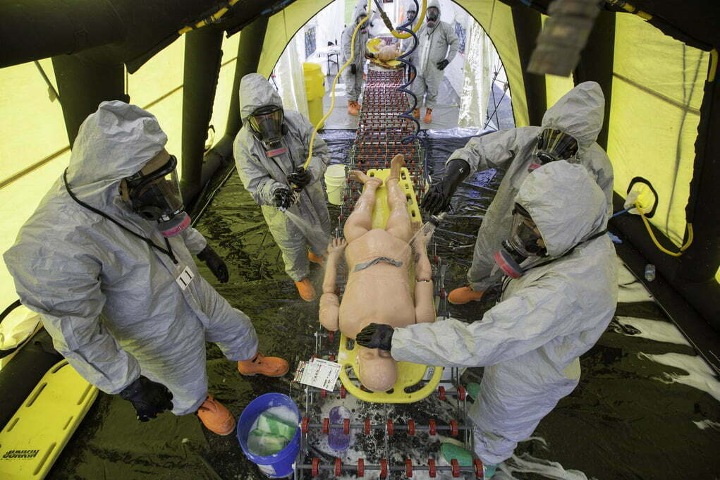 Healthcare professionals in hazmat suits practice decontaminating a simulated patient inside a training tent.