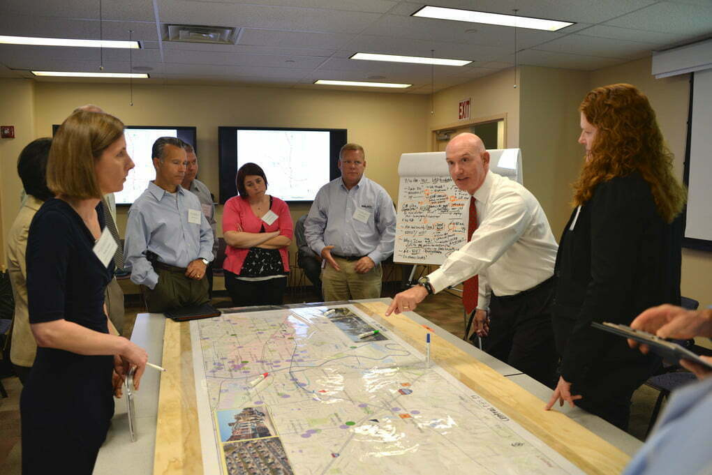 Disaster response stakeholders stand around a table discussing a map.
