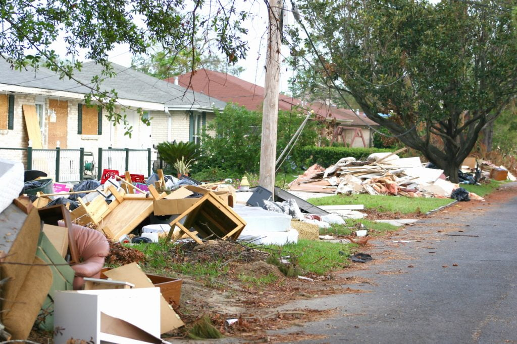 Debris from flooded homes lines a neighborhood street.