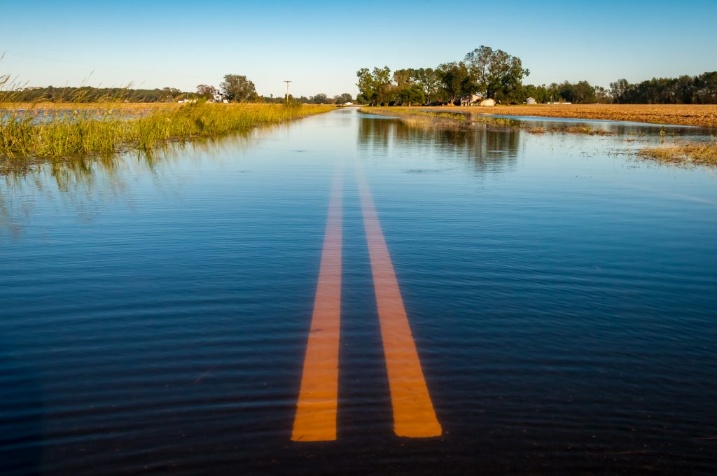 Yellow lines down the middle of a flooded country road.
