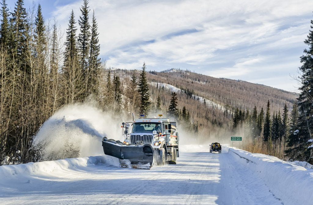 A snow plow clears an icy stretch of road after a snow storm